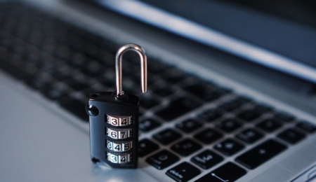 Padlock next to computer highlighting the importance of cyber security.